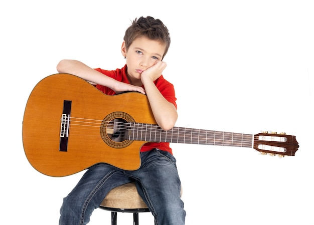 Menino branco triste com um violão nas mãos. a criança não quer se envolver com música