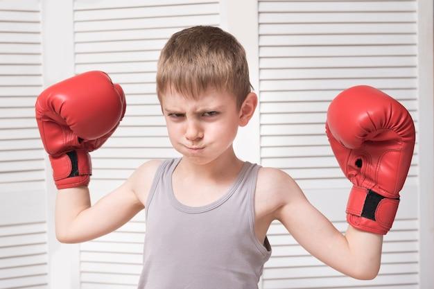 Menino bravo em luvas de boxe vermelhas.
