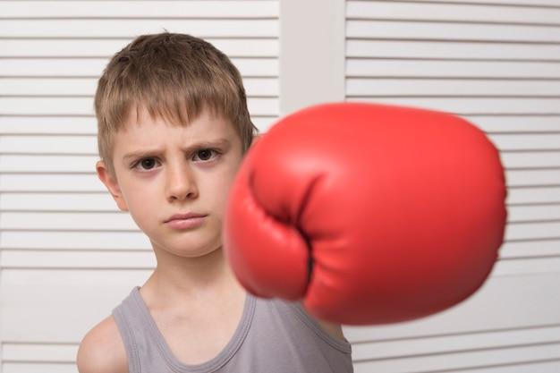 Menino bravo na luva de boxe vermelha. acertar