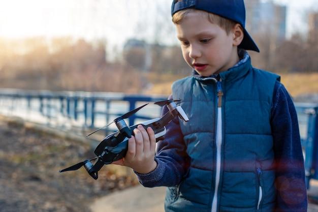 Menino brinca com seu drone no parque