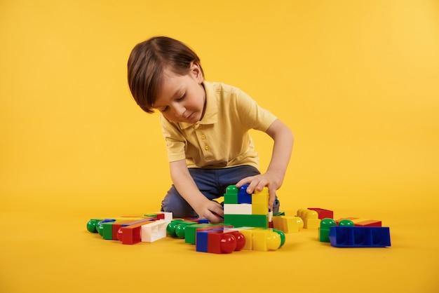 Menino brinca com tijolos de brinquedo de plástico. conceito de lazer de crianças.