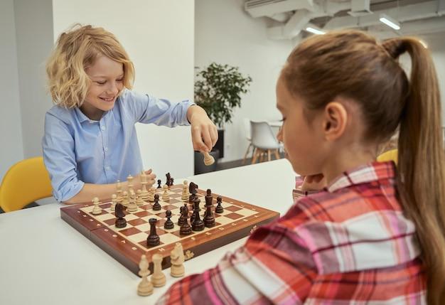 Menino brincalhão caucasiano sorrindo enquanto faz sua jogada jogando xadrez com um amigo sentado