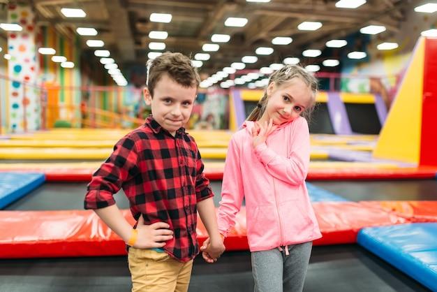 Menino brincalhão e menina no centro de entretenimento infantil. infância feliz