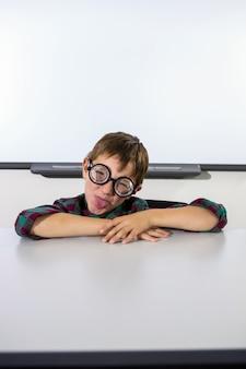 Menino brincalhão, fazendo uma careta na sala de aula