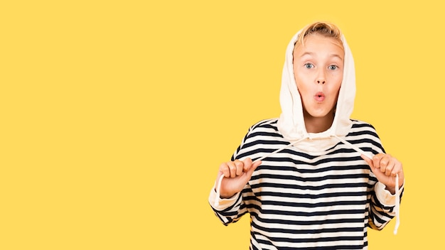 Menino brincalhão, vestindo capuz sobre fundo amarelo