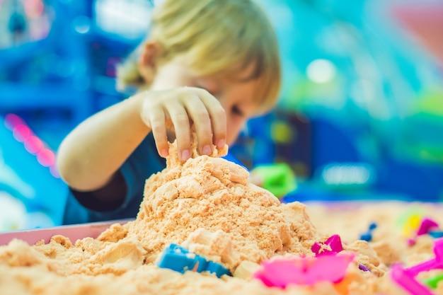 Menino brincando com areia cinética
