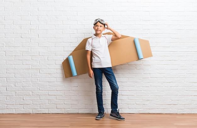 Menino brincando com asas de avião de papelão de costas em pé e pensando uma idéia