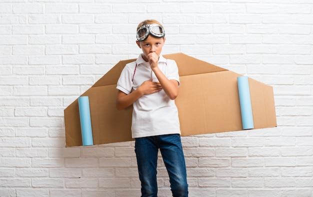 Menino brincando com asas de avião de papelão nas costas está sofrendo com tosse e se sentindo mal