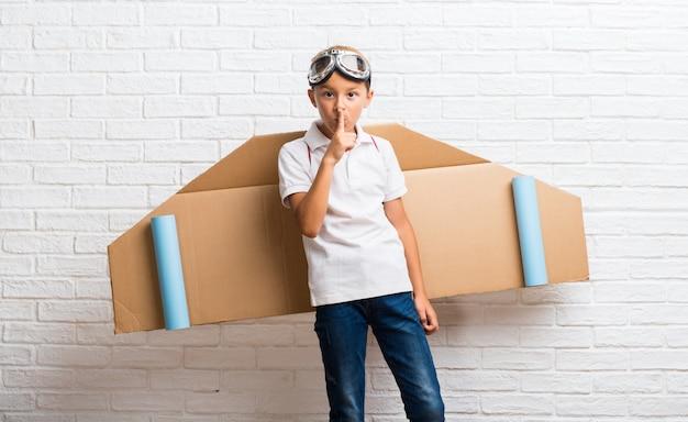 Menino brincando com asas de avião de papelão nas costas, mostrando um sinal de fechar a boca