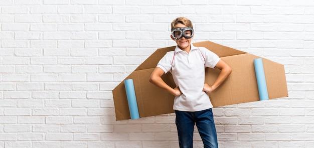 Menino brincando com asas de avião de papelão posando com os braços no quadril