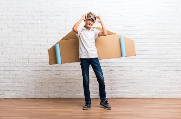 Menino brincando com asas de avião de papelão