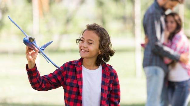 Menino brincando com avião e pais desfocados no parque
