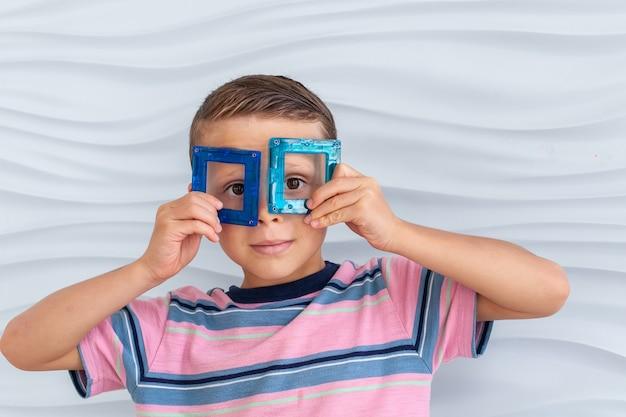 Menino brincando com blocos de brinquedo coloridos o menino coloca os detalhes do construtor no rosto como se fossem óculos