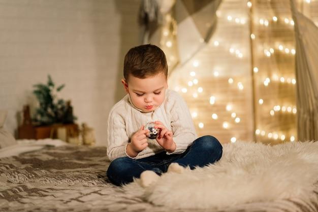 Menino brincando com brinquedos em casa perto da lareira e a árvore de natal.