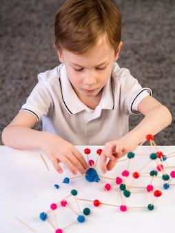 Menino brincando com jogo de átomos coloridos