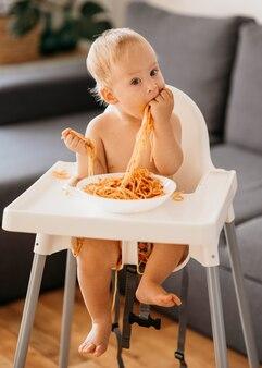 Menino brincando com macarrão em sua cadeira alta