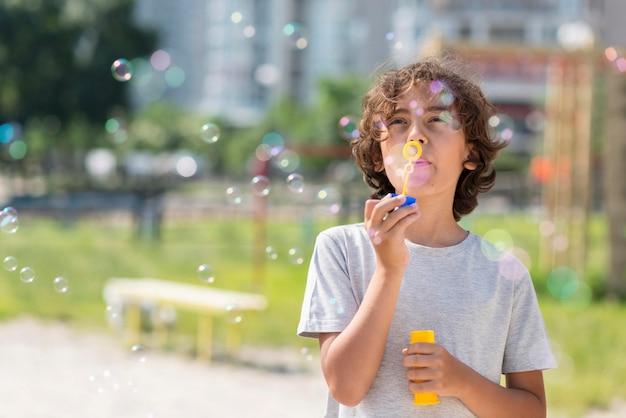 Menino brincando com o ventilador de bolha ao ar livre