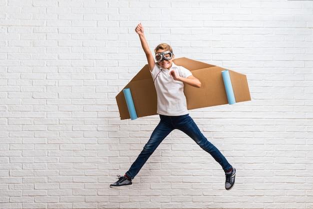 Menino brincando com papelão avião asas pulando
