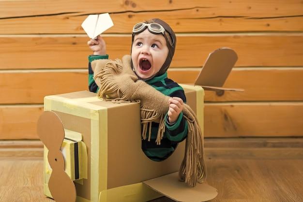 Menino brincando com um avião de papelão na sala de madeira