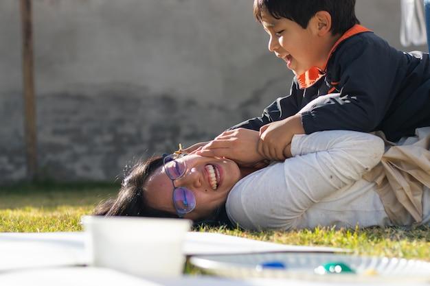 Menino brincando com uma jovem no quintal em um dia ensolarado com objetos para pintar em primeiro plano