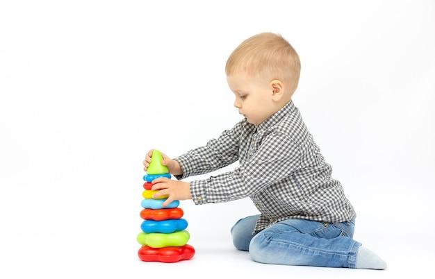Menino brincando de brinquedo isolado no fundo branco