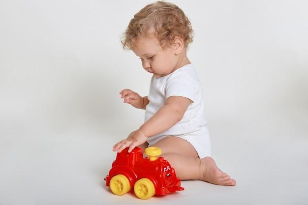 Menino brincando de carro isolado no branco