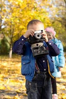 Menino brincando de ser um aspirante a fotógrafo segurando uma câmera vintage contra os olhos
