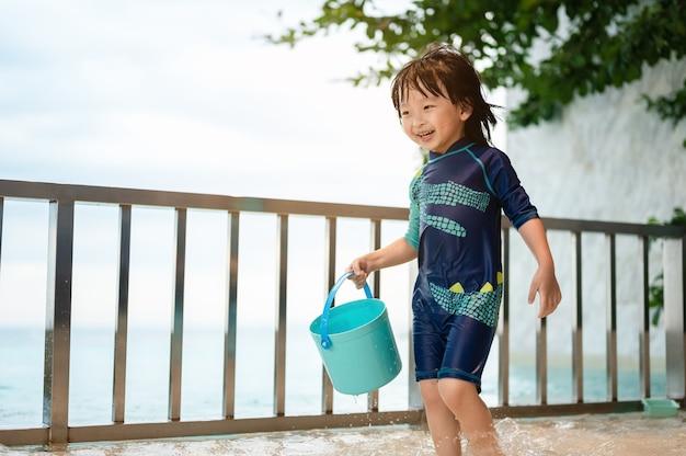 Menino brincando feliz com um balde de brinquedos aquáticos na piscina de um hotel divertindo-se