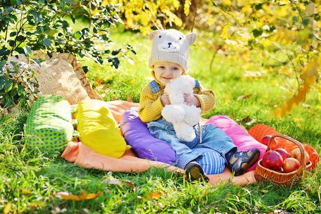 Menino brincando na floresta outonal
