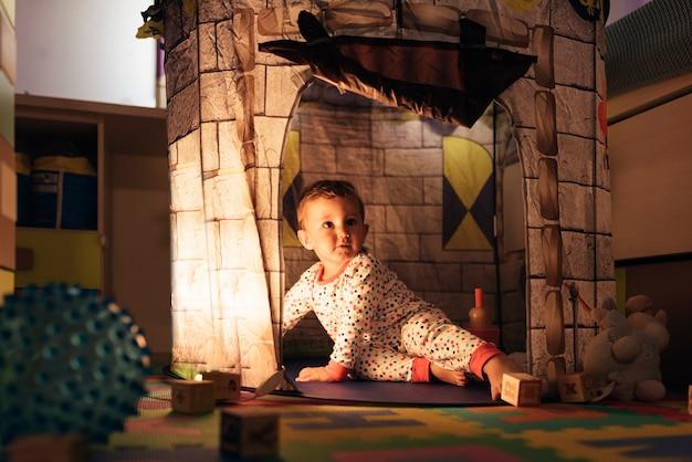 Menino brincando no brinquedo do castelo em casa. conceito de infância.