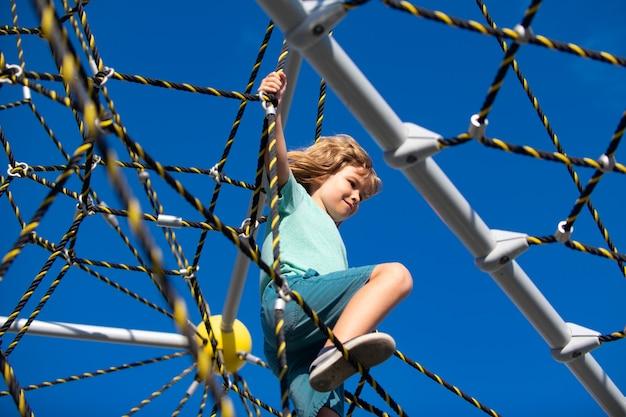Menino brincando no parquinho, crianças brincando no parque de cordas ao ar livre