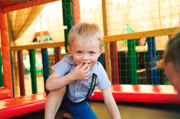 Menino brincando no playground, no labirinto das crianças.