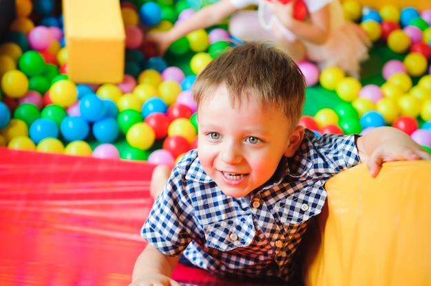 Menino brincando no playground, no labirinto infantil com bolas