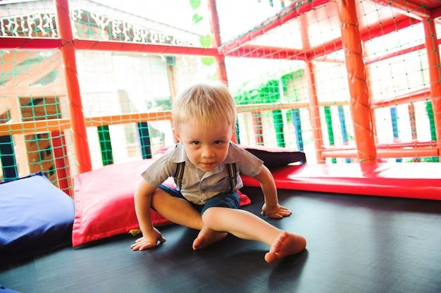 Menino brincando no playground, no labirinto infantil
