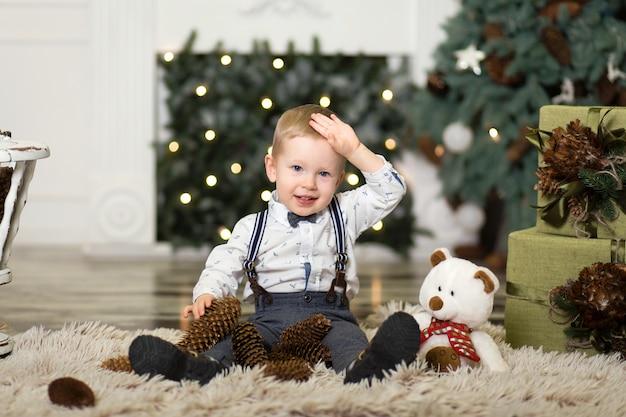 Menino brincar com pinhas perto de uma árvore de natal.