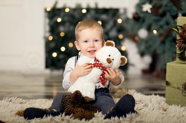 Menino brincar com ursinho de pelúcia perto de uma árvore de natal.