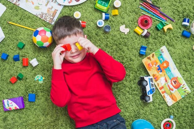 Menino, brinquedos jogando, ligado, chão