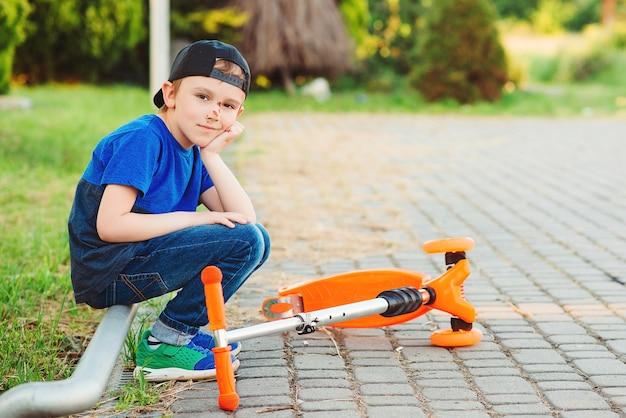 Menino caindo de sua scooter. criança se machucando ao andar de scooter. criança despreocupada em uma caminhada. menino aprende a andar de scooter.