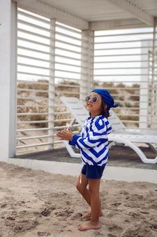 Menino caminha na praia com areia em uma espreguiçadeira com uma jaqueta azul listrada e óculos escuros em