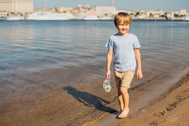 Menino caminhando ao longo da costa