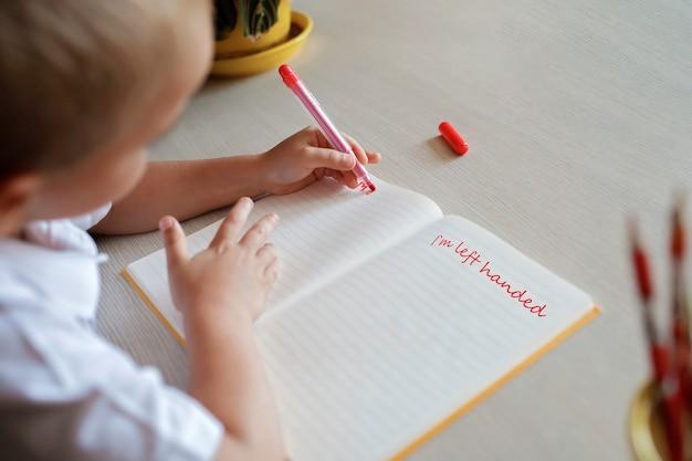 Menino canhoto feliz escrevendo no livro de papel com a mão esquerda dia internacional do canhoto