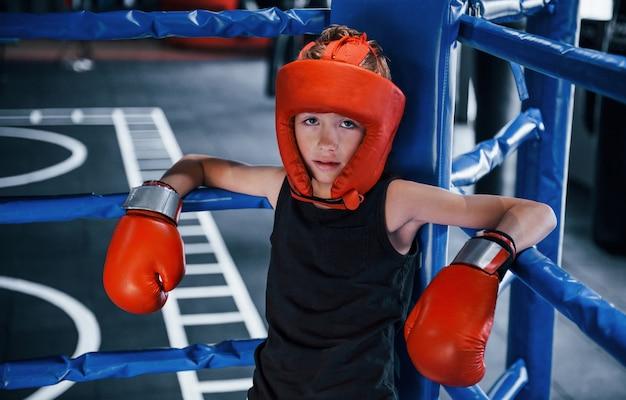 Menino cansado com equipamento de proteção apoiado nos nós do ringue de boxe.
