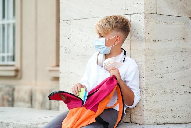 Menino cansado com máscara de segurança depois das aulas