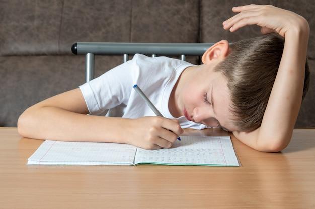 Menino cansado deitado em uma mesa escrevendo dever de casa ou se preparando para um exame, vista frontal