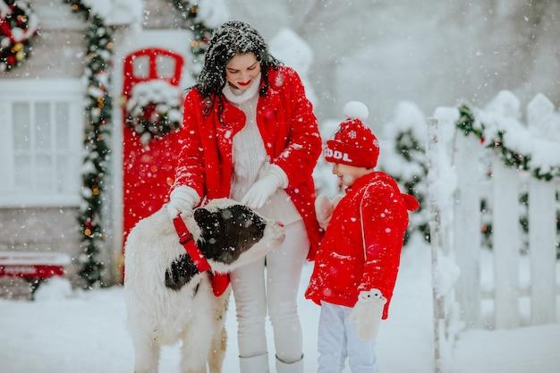 Menino, casaco e mulher morena posando com um pequeno touro no rancho de inverno com decoração de natal. nevando.
