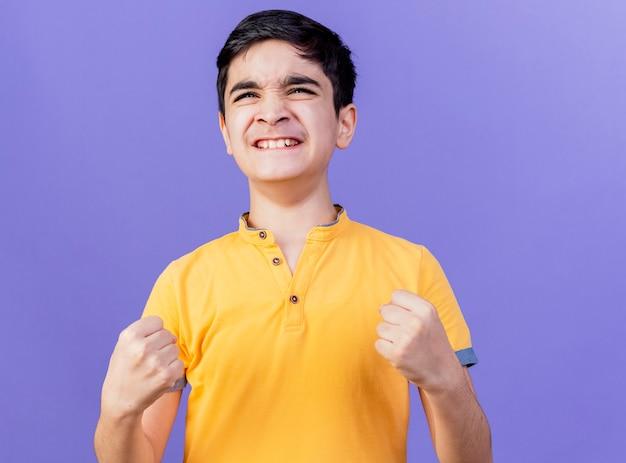 Menino caucasiano alegre olhando para o lado fazendo gesto de sim, isolado em um fundo roxo com espaço de cópia