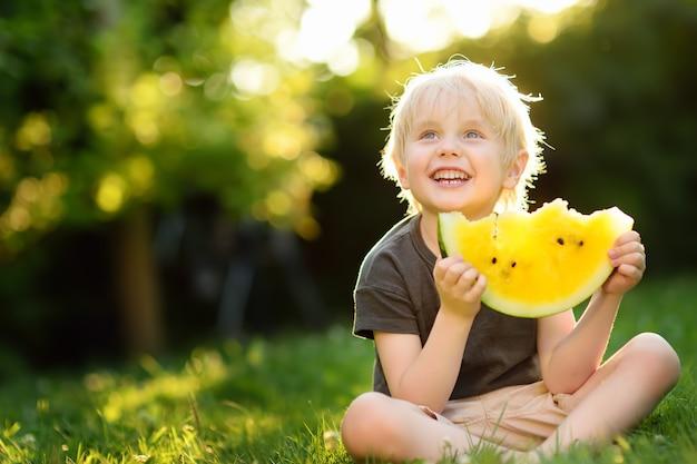 Menino caucasiano bonito com cabelos loiros comendo melancia amarela ao ar livre