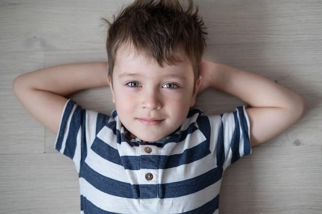 Menino caucasiano bonito pré-escolar deitado no chão. fechar-se..
