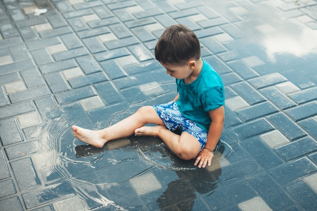 Menino caucasiano brincando com água no chão do quintal.