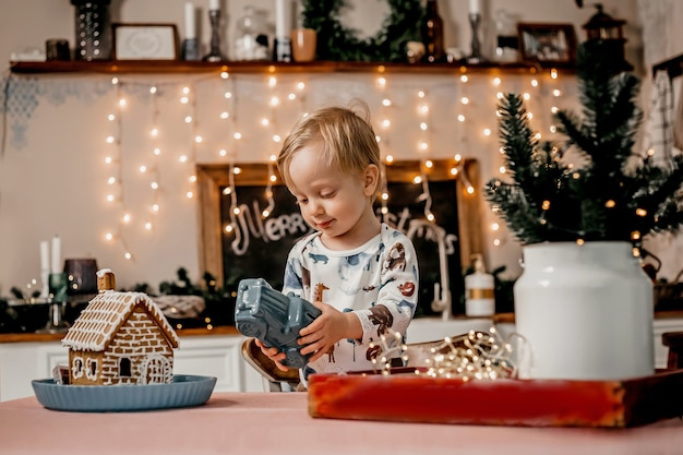 Menino caucasiano brincando com um carro enquanto está na cozinha com decoração de ano novo e guirlandas